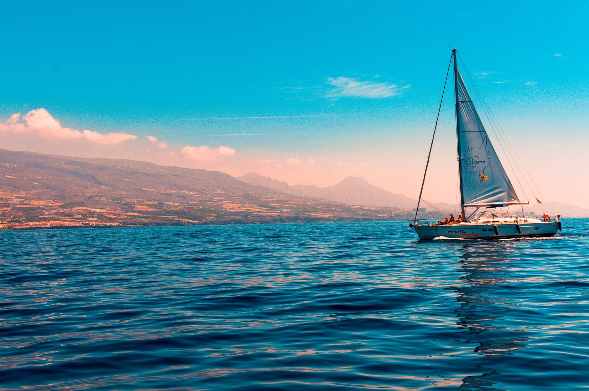 sailboat sailing on water near island