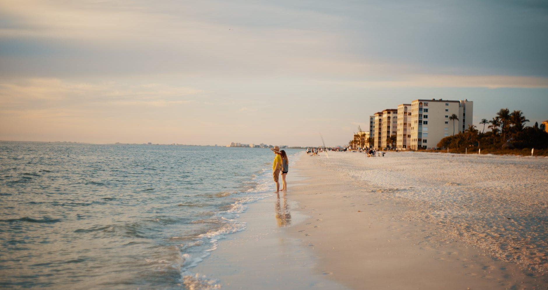 anonymous couple standing on sandy seashore at sundown