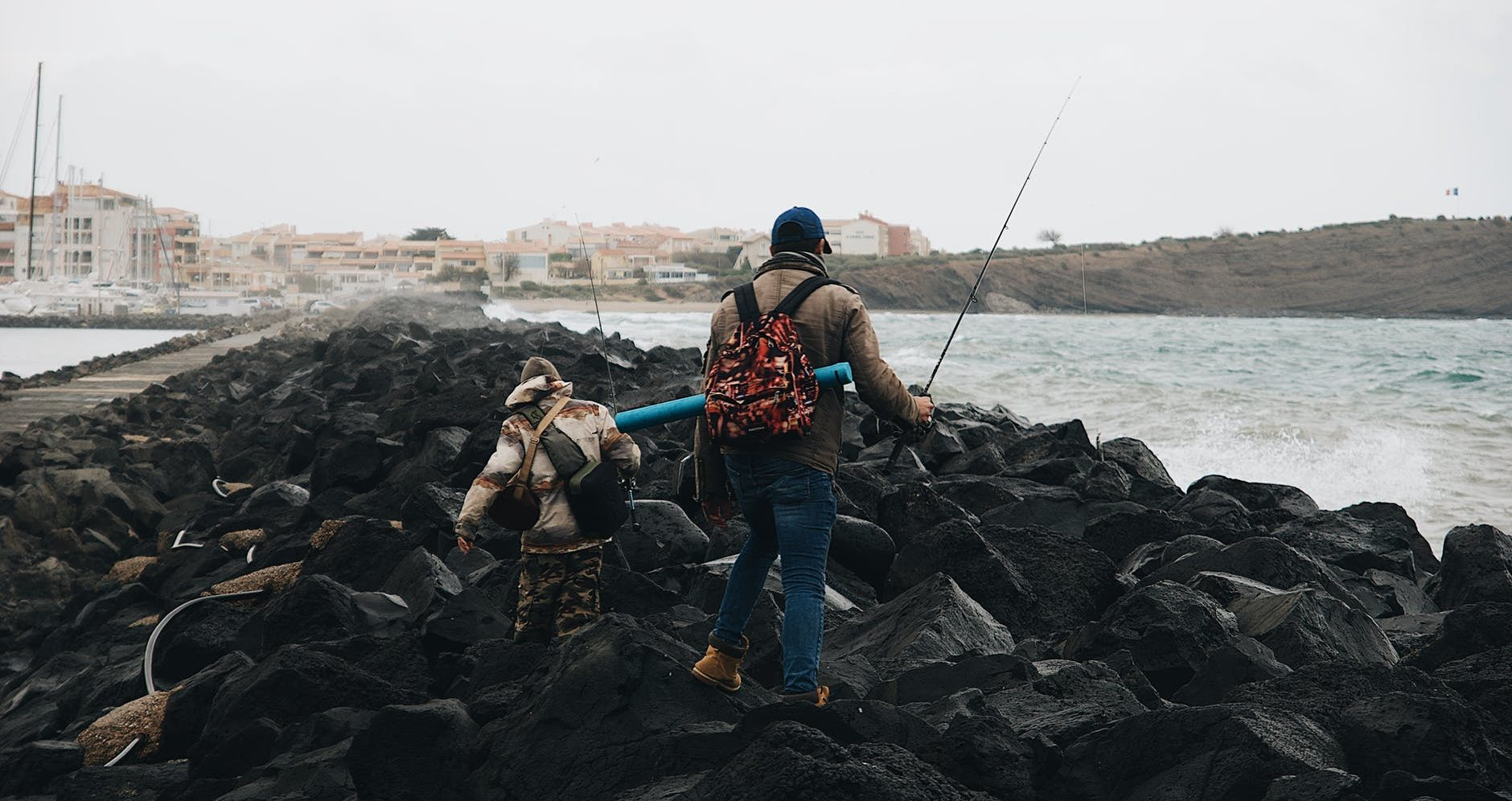 man in blue denim jeans and blue backpack standing on rocky shore