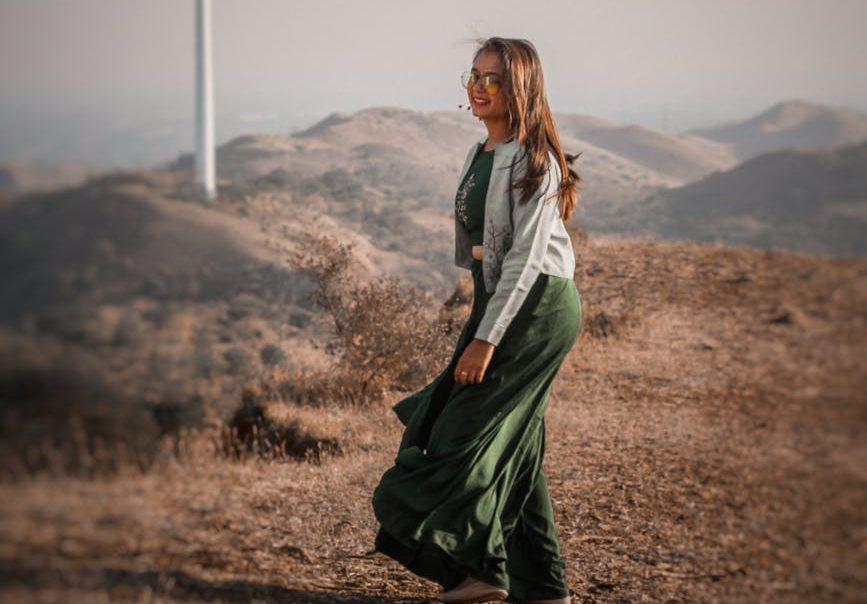 stylish woman standing near wind generator